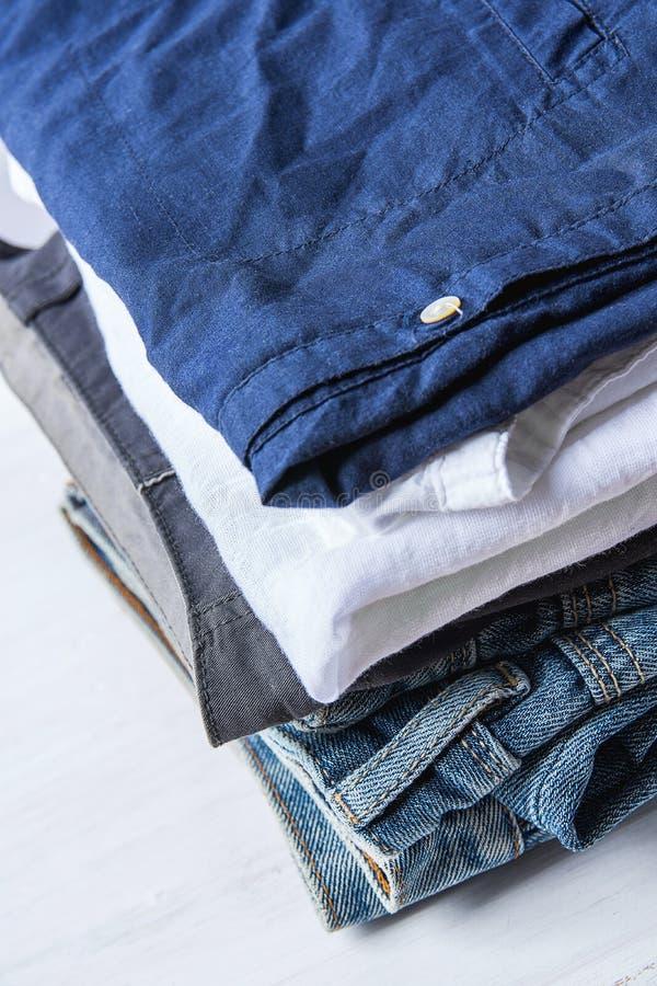 Bunthög av vikta jeansbomullsflåsanden och skjortor på den vita Wood bakgrundshyllagarderoben Autentisk klassisk stil för Eco mod arkivfoton