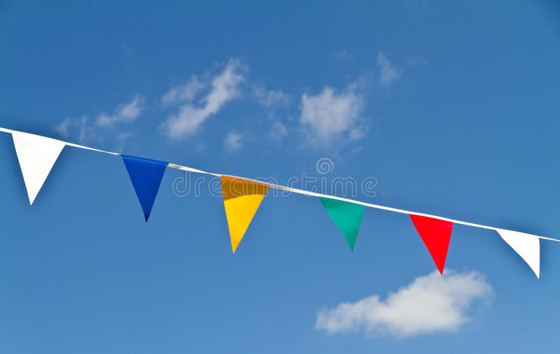 Bunting. Brightly coloured bunting against a blue sky with fluffy clouds stock image