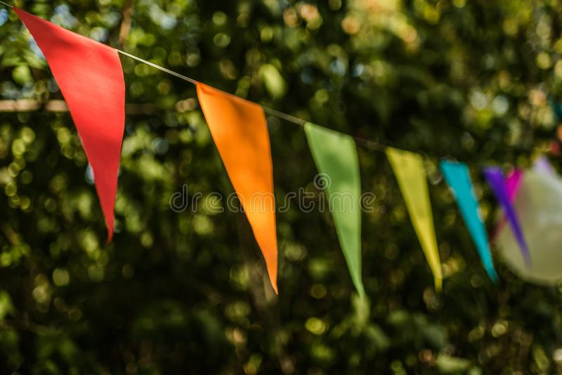 Bunting flags. Colorful paper bunting flags and balloons hanging for trees at a summer party royalty free stock photography