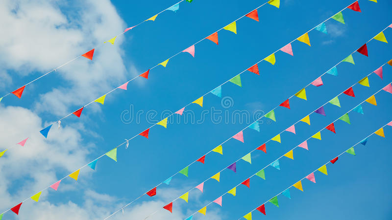 Bunting flags. Colorful small bunting flags flying on blue sky background royalty free stock photo