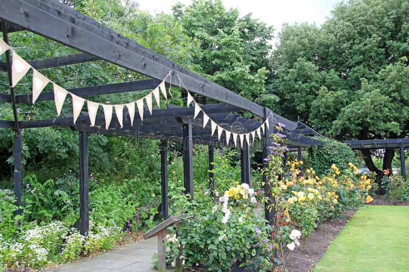 Bunting party garden. Photo of party bunting tied to a pergola frame in country garden. july 2016 royalty free stock photo