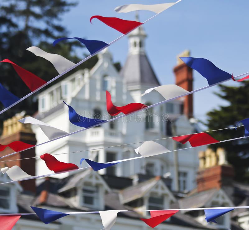 A Bunting of Red, White and Blue Fourth of July Flags. Victorian Architecture Behind, Main Street, Anytown, USA stock image