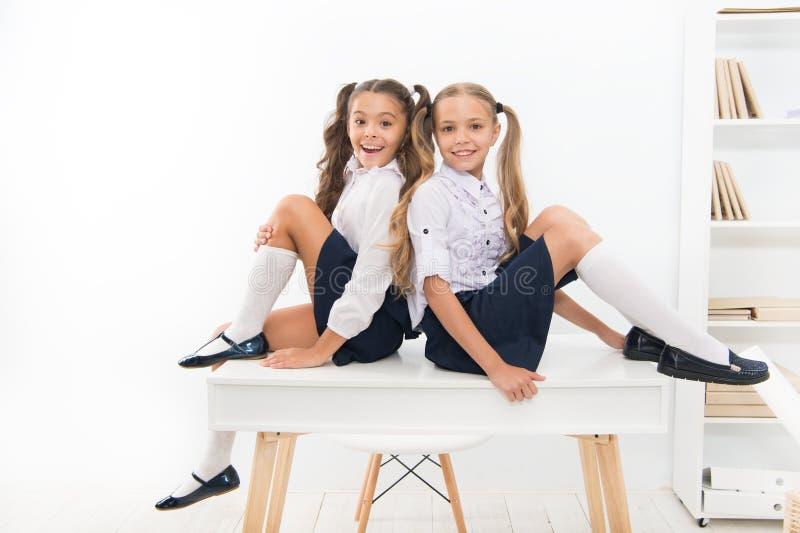 Buntowniczy duch Szkolny klub Małych uczennica kolegów z klasy życzliwi dzieciaki Uczennica przyjaciele siedzą na biurku najlepsz obraz stock
