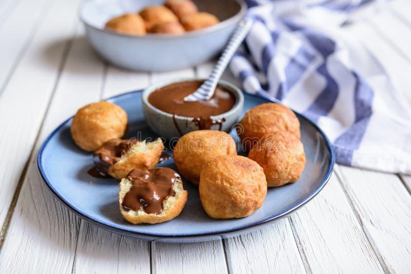 Bunuelos - pasteles fritos colombianos tradicionales con la salsa de chocolate foto de archivo