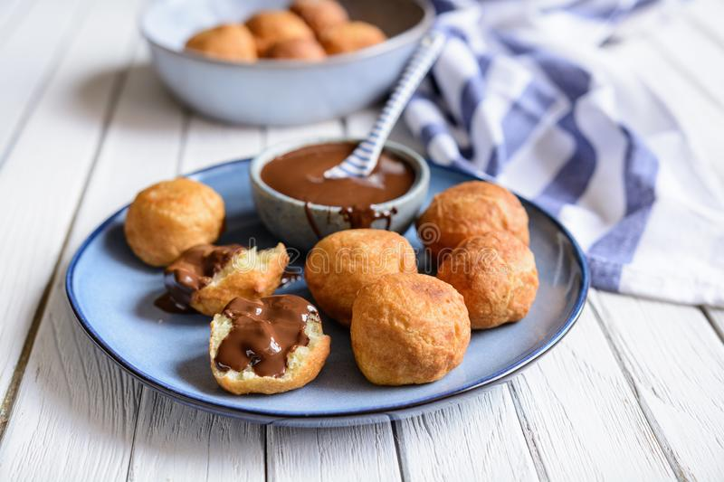 Bunuelos - traditional Colombian deep fried pastry with chocolate sauce stock photo