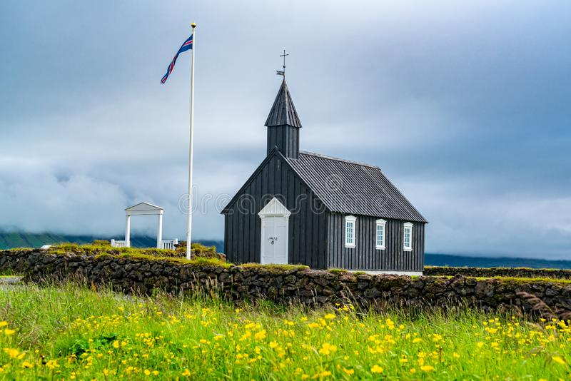 Buoakirja Black Church of Budir. With the field of flowers in summer rainy day at the western region of Iceland royalty free stock photography