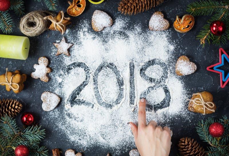 Buon anno 2018 scritto sui biscotti del pan di zenzero delle decorazioni di Natale e della farina su fondo di pietra scuro Cartol fotografia stock libera da diritti