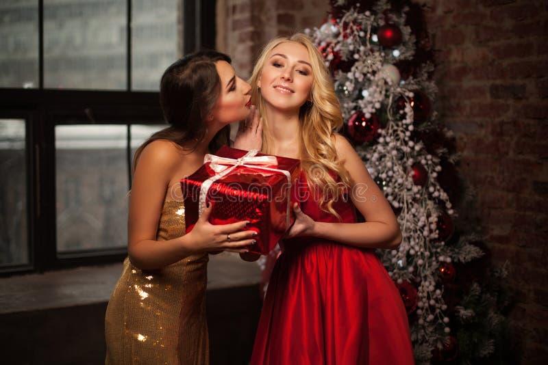 Buon anno a voi due belle giovani donne nel Natale di una celebrazione con presente e kisess Partito del ` s del nuovo anno Natal fotografie stock libere da diritti