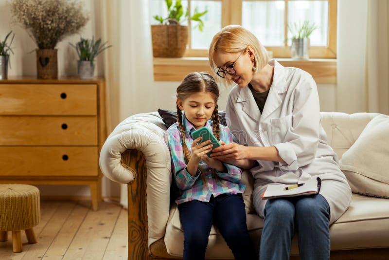 Buon-appello del medico che aiuta una ragazza a giocare un gioco del telefono fotografie stock