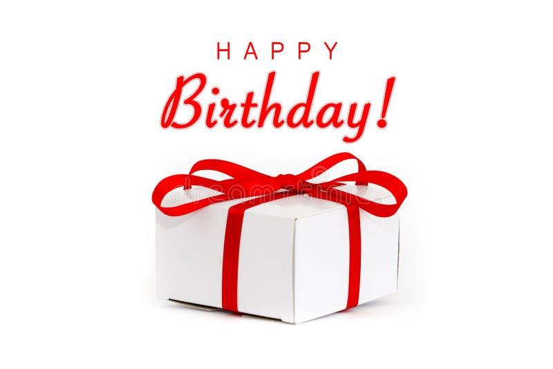 Buon compleanno! contenitore di regalo del cartone di bianco e del messaggio di testo con il nastro rosso decorativo e l'arco leg immagini stock libere da diritti