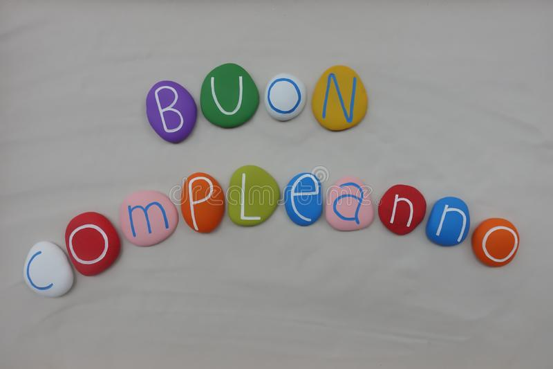 Buon Compleanno, joyeux anniversaire italien avec les pierres colorées au-dessus du sable blanc image libre de droits