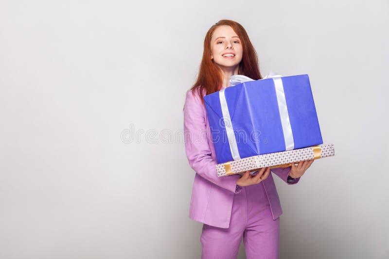 Buon compleanno! La ragazza sveglia dai capelli rossi che tiene i suoi regali ed ha fotografia stock