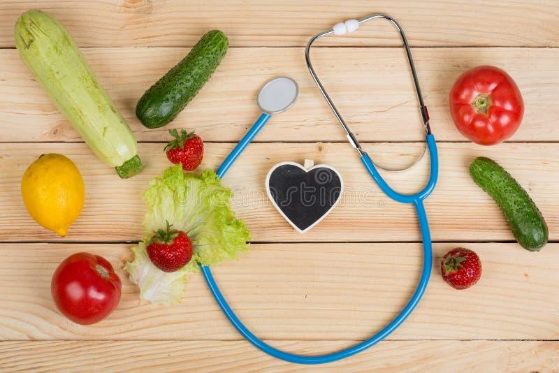 Buon concetto di dieta e sano - lavagna nella forma di cuore, stetoscopio e verdure, frutta e bacche fotografie stock libere da diritti