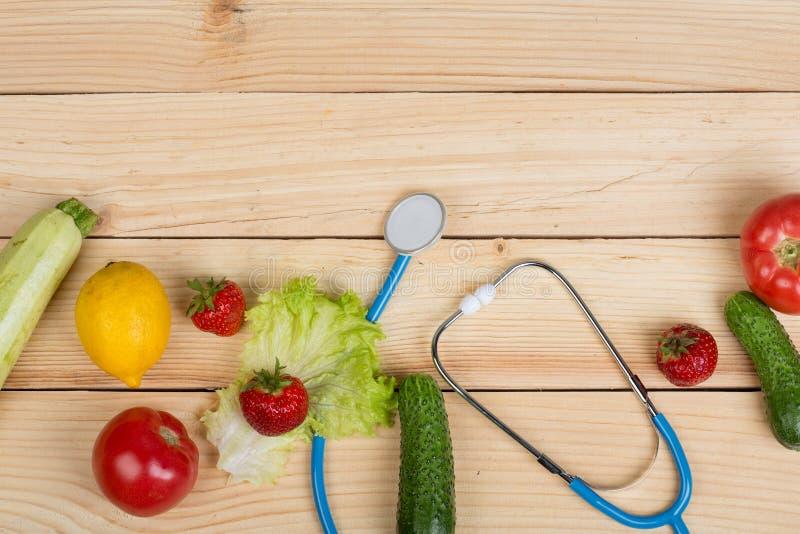 Buon concetto di dieta e sano - stetoscopio e verdure, frutta e bacche sulla tavola fotografia stock