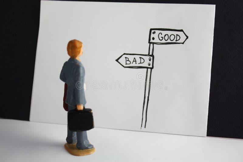 Buon contro il cattivo modo L'uomo miniatura considera l'indicatore stradale disegnato a mano e decide circa futuro Buon, diaboli fotografia stock libera da diritti