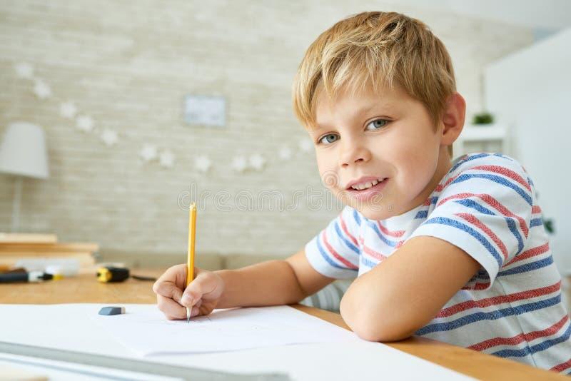 Buon Little Boy che studia a casa immagine stock