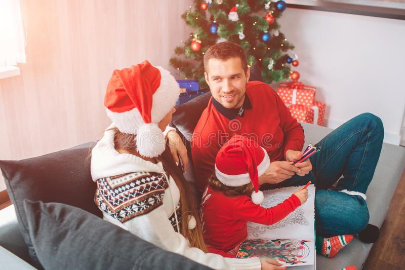 Buon Natale e buon anno Immagine adorabile della famiglia che si siede insieme sul sofà Sguardo dei genitori ad a vicenda Donna immagine stock libera da diritti