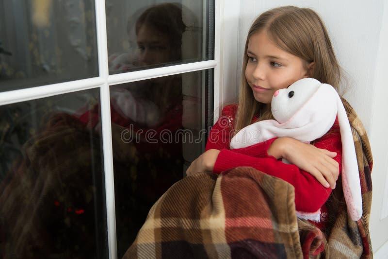 Buon Natale e buon anno Piccolo bambino con il giocattolo del coniglio alla finestra Piccolo amico del giocattolo della tenuta de fotografia stock