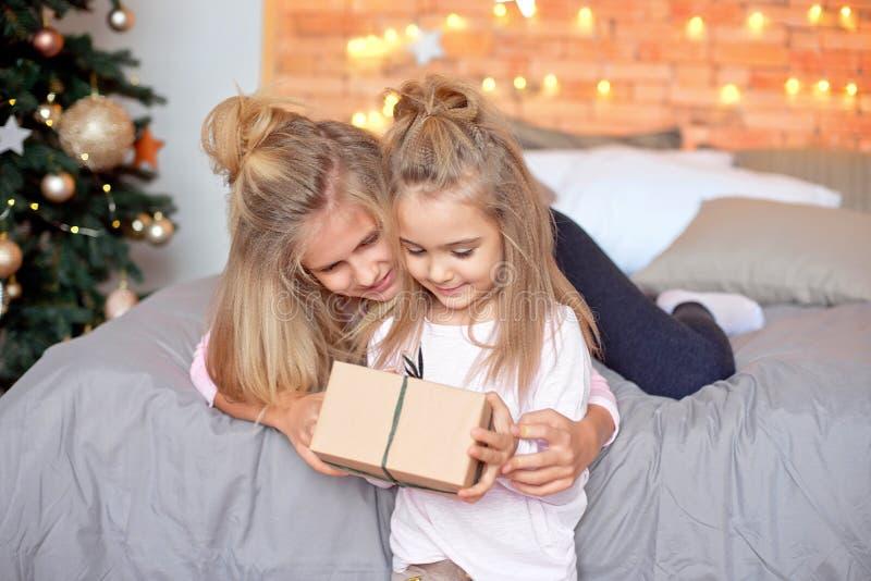 Buon Natale e feste felici Bambini svegli allegri che aprono i regali Bambini divertendosi vicino all'albero di mattina fotografia stock