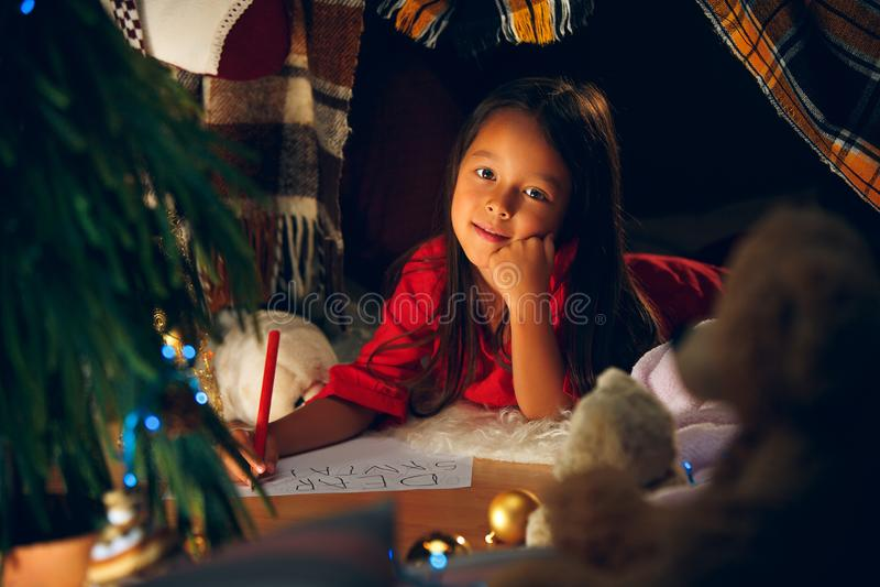 Buon Natale e feste felici La ragazza sveglia del piccolo bambino scrive la lettera a Santa Claus vicino all'albero di Natale fotografie stock