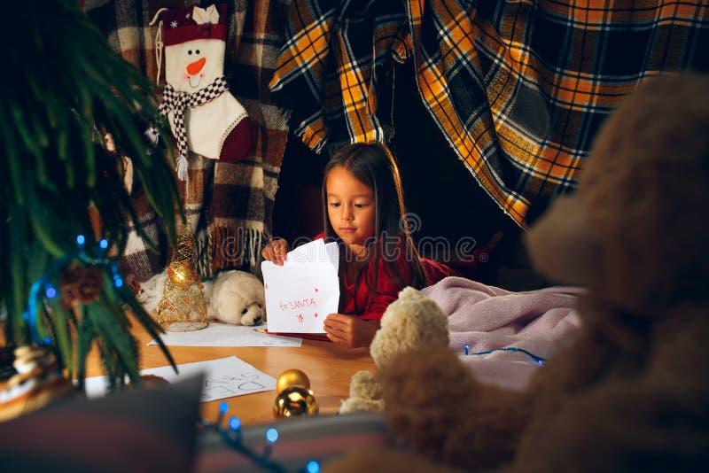 Buon Natale e feste felici La ragazza sveglia del piccolo bambino scrive la lettera a Santa Claus vicino all'albero di Natale fotografie stock libere da diritti