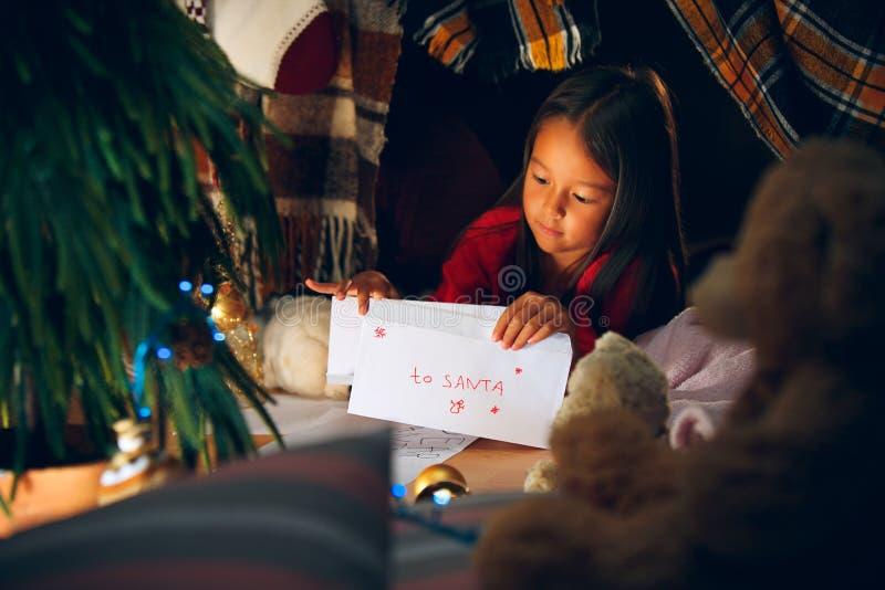 Buon Natale e feste felici La ragazza sveglia del piccolo bambino scrive la lettera a Santa Claus vicino all'albero di Natale fotografia stock libera da diritti