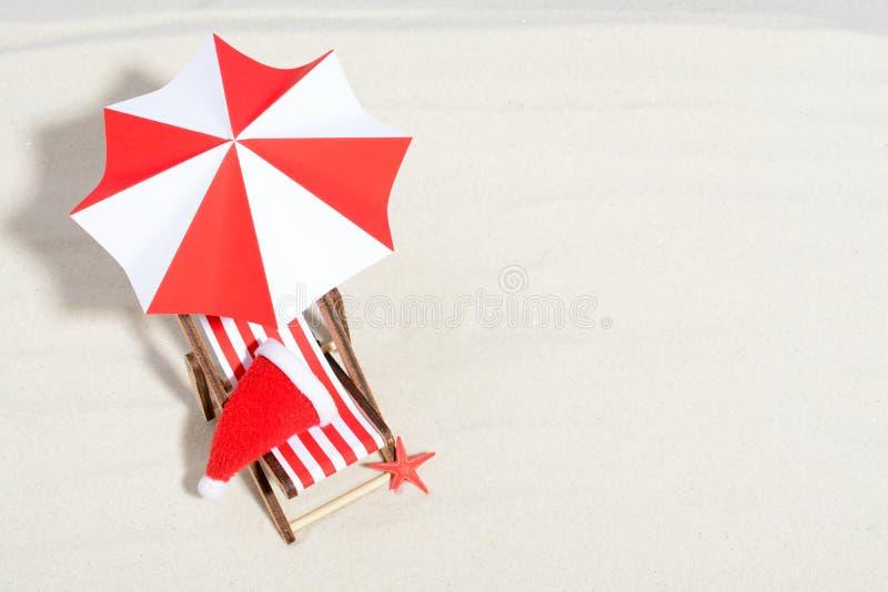Buon Natale sul concetto della spiaggia Sedia di salotto con l'ombrello ed il cappello di Santa immagine stock libera da diritti