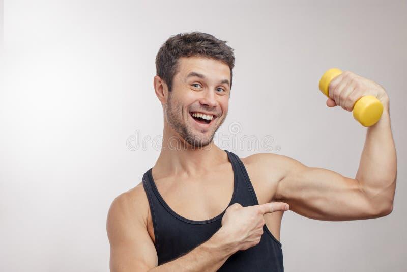 Buon risultato dopo la formazione un uomo allegro sta indicando le sue forti armi immagini stock