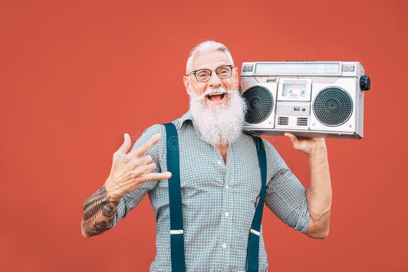 Buon uomo anziano che ascolta musica con boombox outdoor - Un pazzo hipster maschio che si diverte a ballare con lo stereo vintag fotografia stock libera da diritti