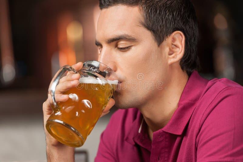 Buona birra. Ritratto dei giovani bei che bevono birra alla p immagini stock libere da diritti
