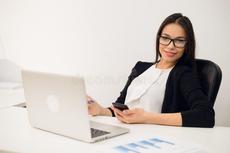 Buona conversazione di affari Giovane bella donna allegra in vetri che parla sul telefono cellulare e che per mezzo del computer  fotografie stock libere da diritti
