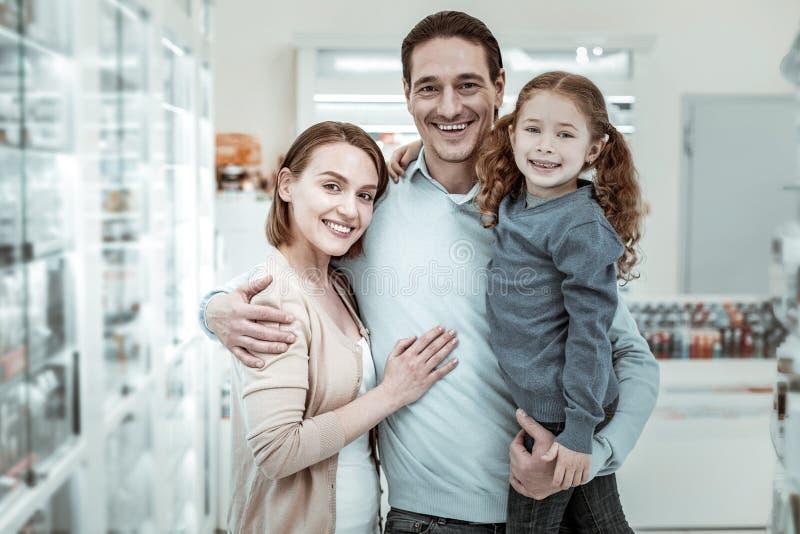 Buona famiglia coccolante e sorridente in farmacia fotografia stock