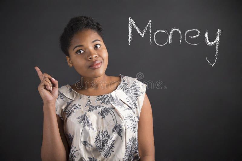 Buona idea della donna afroamericana circa soldi sul fondo della lavagna fotografia stock libera da diritti