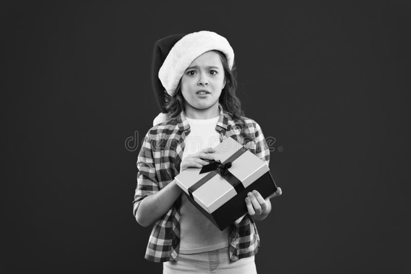 Buone vacanze invernali Piccola ragazza sconvolta Presente per Natale Infanzia Bambina di santa col cappello rosso Natale immagini stock libere da diritti