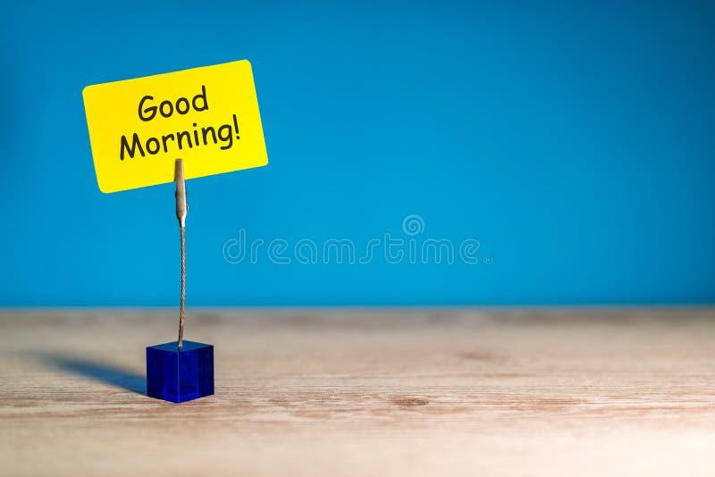 Buongiorno - desiderio per un buon giorno Nota a carta gialla a fondo blu Con spazio vuoto per testo, modello e fotografia stock libera da diritti
