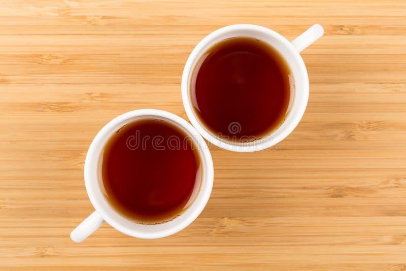 Buongiorno, due tazze bianche di tè isolate su un fondo di legno hanno sparato da sopra, prima colazione immagine stock libera da diritti