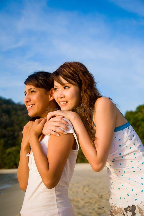 Buoni amici che abbracciano insieme sguardo al tramonto fotografie stock libere da diritti