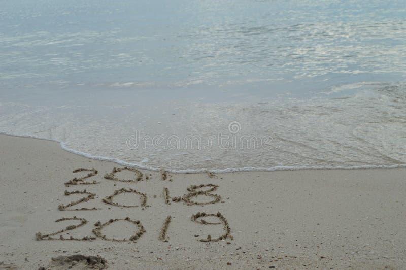 Buoni anni 2017, 2018 e 2019 scritti a mano sulla sabbia fotografia stock libera da diritti