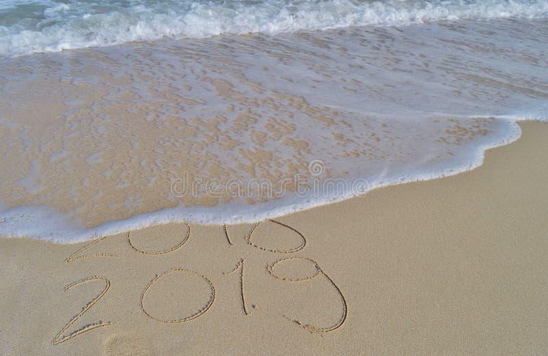 Buoni anni 2018 e 2019 scritti a mano sulla sabbia fotografia stock