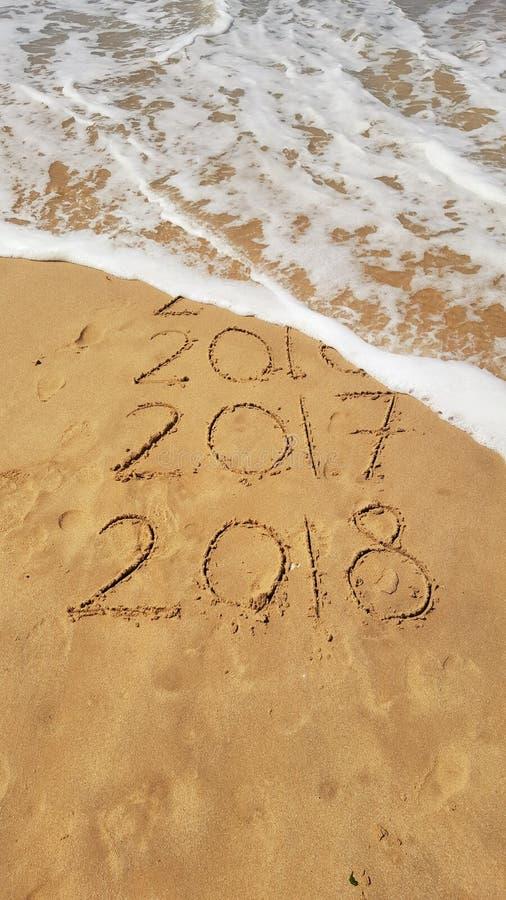 Buoni anni 2017 e 2018 scritti a mano sulla sabbia con un'onda che viene a cancellare 2016 fotografia stock