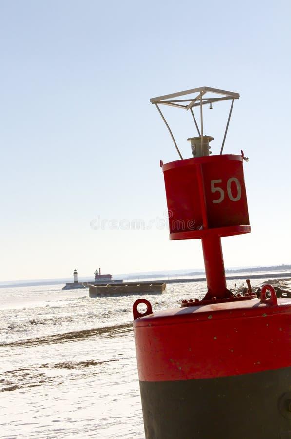 Buoy con la greppia ed i fari sul pilastro lungo il channe di trasporto fotografie stock