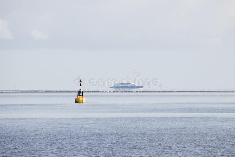 buoy en el mar de Wadden y balsee a la isla Vlieland de wadden fotografía de archivo