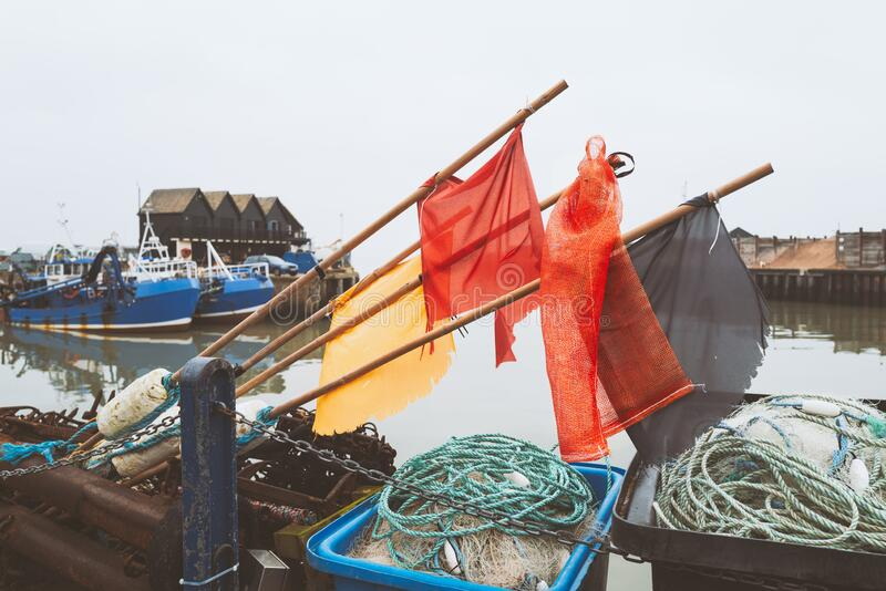 Buoy flag makers on poles above rope and fishing next baskets in Whitstable harbour. Fisherman huts and fishing boats can be seen stock images