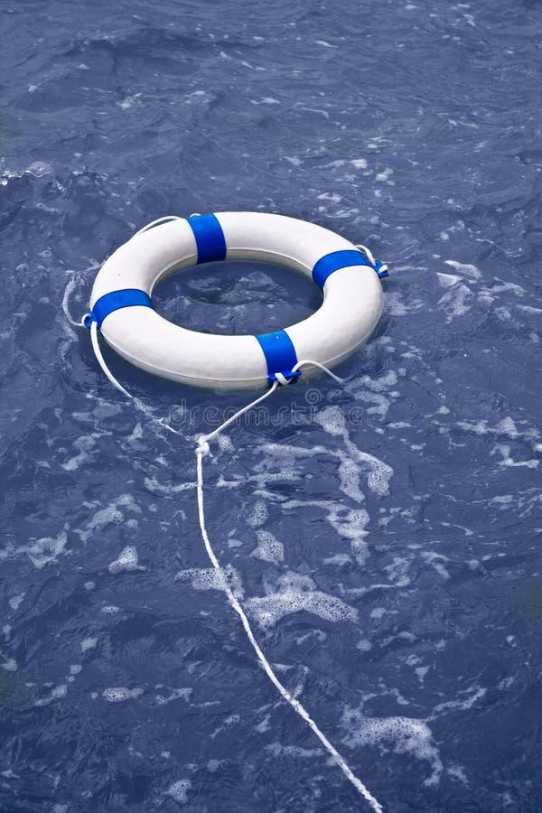 Buoy, lifebelt, lifesaver floating in ocean as help equipment. Buoy, lifebelt, lifesaver floating in blue ocean as help equipment stock images