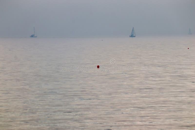 Buoy no meio do oceano no dia enevoado com os barcos distantes no horiz fotografia de stock royalty free