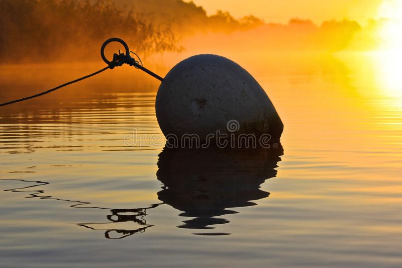 A buoy in the sunset royalty free stock image