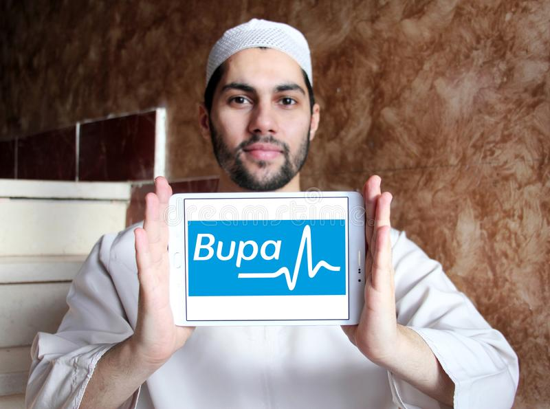 Bupa healthcare company logo. Logo of Bupa healthcare company on samsung tablet holded by arab muslim man. Bupa is an international healthcare group royalty free stock images