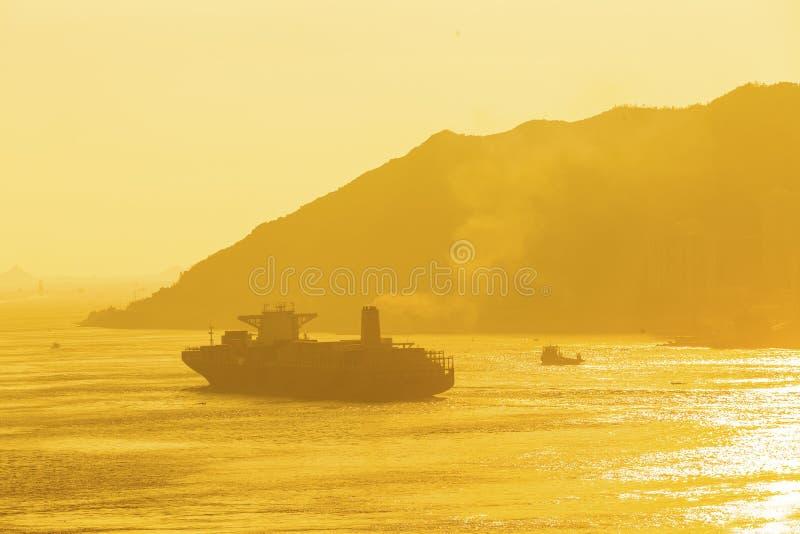 Buque de carga bajo puesta del sol imagenes de archivo