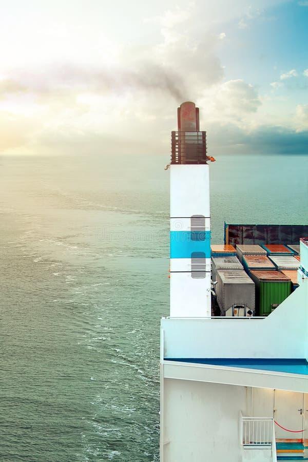 Buque de carga con una navegación del tubo que fuma en el mar foto de archivo libre de regalías
