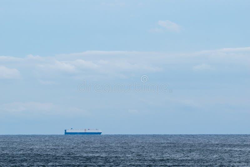 Buque de carga en el agua tranquila, cruzando el horizonte en un día soleado hermoso imagen de archivo libre de regalías